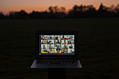 Friends video chatting on laptop screen in garden at dusk