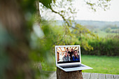 Family video chatting on laptop screen on balcony