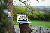Face mask hanging next to video chat on laptop on balcony