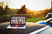 Friends video chatting on laptop screen on top of car