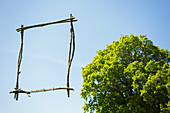 Wood stick picture frame against sunny blue sky with tree