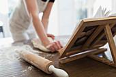 Woman kneading dough at cookbook