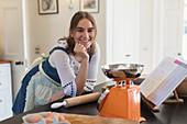 Portrait happy teenage girl baking in kitchen