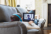 Teenage girl video chatting with friends on living room sofa
