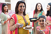 Portrait happy mother and daughter in Indian saris with food
