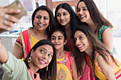 Happy Indian women and girls in saris taking selfie