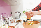 Woman squeezing lemon over bowl of food in kitchen