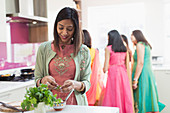 Indian woman in sari and bind cooking food with family