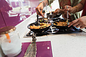 Indian women cooking food at stove in kitchen