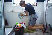 Woman cleaning bathtub in bathroom