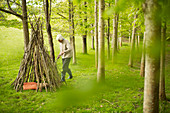 Senior woman making branch teepee in woodland