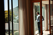 Businessman using smart phone at sunny window