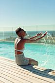 Carefree young woman splashing water