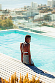 Serene young woman at sunny rooftop swimming pool