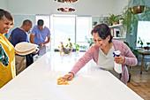 Happy women friends cleaning kitchen island