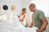 Couple making bed together in bedroom