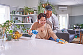Mature couple cleaning kitchen island