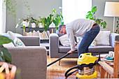 Mature man vacuuming living room