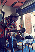 Male musician with laptop and guitar garage