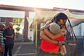 Happy friends hugging in sunny parking lot
