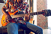 Male musician playing electric guitar in garage