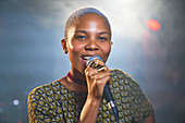 Portrait female musician singing into microphone
