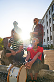 Portrait confident musicians in sunny parking lot
