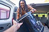 Happy male musician loading drum into van