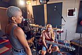 Smiling musicians practicing in recording studio