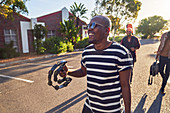 Happy male musician with tambourine on street