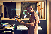 Male musician playing guitar in recording studio