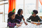 Happy mother and sons making Christmas cookies