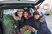 Mother and children with Christmas tree and wreath