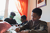 Boy writing Christmas cards at table