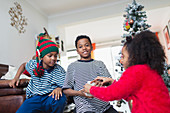 Brothers and sister opening Christmas gifts