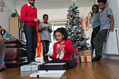 Family watching girl open Christmas gifts