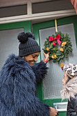 Mother and daughter hanging Christmas wreath