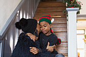 Mother kissing son in Christmas hat on stairs