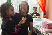 Mother and daughter eating Christmas cookie