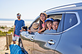 Portrait happy family in car at sunny beach