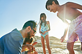 Happy family playing on sunny beach