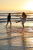 Mother and son splashing in ocean surf at sunset