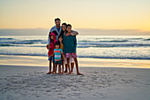 Portrait happy family on ocean beach at sunset