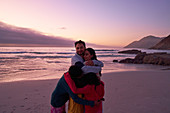 Family hugging on sunset ocean beach, Cape Town