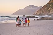 Family walking on ocean beach, South Africa