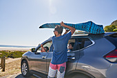 Man removing surfboard from top of car