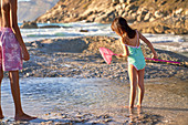 Girl with fishing net playing in tide pool