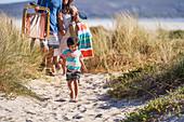 Happy boy walking on sunny beach path