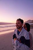 Affectionate couple hugging on ocean beach