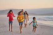 Happy family running on ocean beach